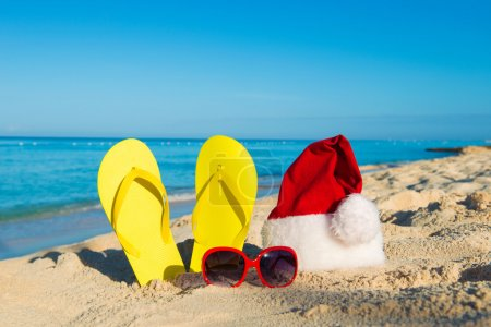 Christmas vacation at sea. Happy  New Year holidays. Santa hat, sandals, sunglasses on sandy beach