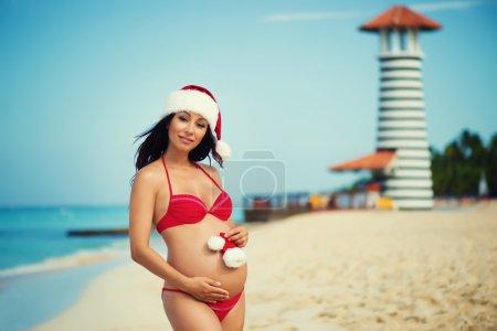 Pregnant woman in a red bathing suit and a Christmas santa hat on the sea coast