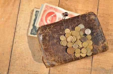 Photo pour Sac à main en cuir vintage avec une poignée de pièces et de billets sur le fond de planches en bois - image libre de droit