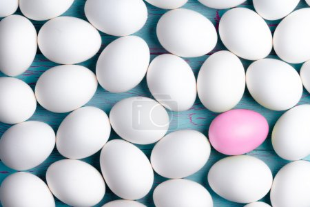 Large number of white Easter eggs and one pink one