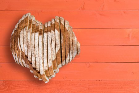 Yummy loaf shaped as heart over orange paneling
