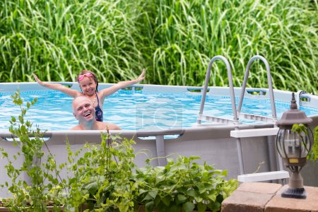 Photo for Happy father and his cute little five year old daughter in an above ground swimming pool laughing and smiling - Royalty Free Image