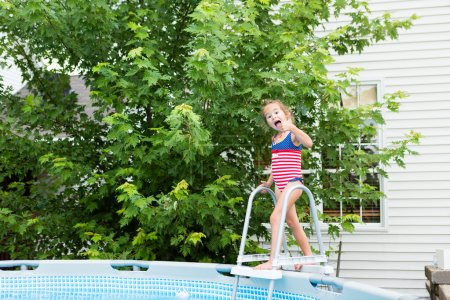 Happy five year old girl entering swimming pool