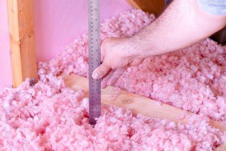 Foto de Comprobación de la eficiencia energética de su casa midiendo el espesor del aislamiento de fibra de vidrio en el ático - Imagen libre de derechos