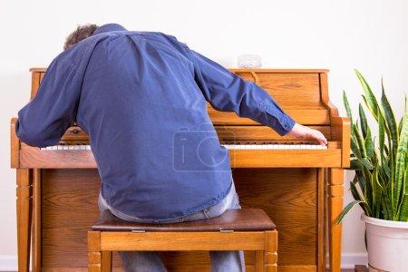Photo pour Homme enthousiaste jouant du piano avec l'enthousiasme s'étendant à chaque extrémité du clavier, vue de derrière de lui s'asseyant sur le tabouret se penchant vers l'avant - image libre de droit