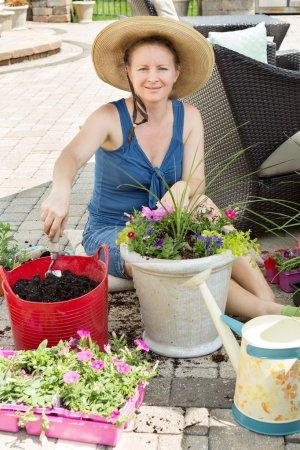 Smiling lady gardener potting up spring flowers