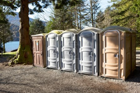Photo for Portapotty, or portable enclosed plastic portable toilet with chemicals and deodorizers in a tank, in a park yard for public convenience - Royalty Free Image
