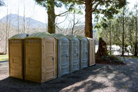 Photo for Row of public Portapotty toilets in a park for public ablutions using chemical toilets and deodorizers for smell, standing in the shade of a tree with closed doors - Royalty Free Image