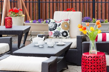 Photo pour Tea served on an outdoor patio between flowers in flowerpots and tulips in a vase with comfortable armchairs and cushions for a relaxing break - image libre de droit