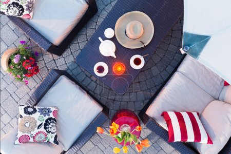 Photo pour Relaxing evening on the patio having tea by candlelight with comfortable deep seating armchairs and colorful flowers around a table set with tea and a straw sunhat, overhead view - image libre de droit