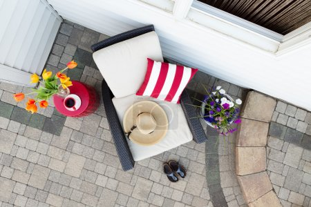 Photo pour Taking a relaxing tea break in a deep seating patio set with a comfortable armchair flanked by colorful spring flowers with a sunhat and garden shoes on a brick paved outdoor patio, overhead view - image libre de droit