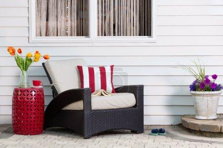 Photo pour Teatime prenant une pause détente sur le patio extérieur dans un fauteuil confortable profond avec des fleurs de printemps colorées profitant du soleil saisonnier - image libre de droit
