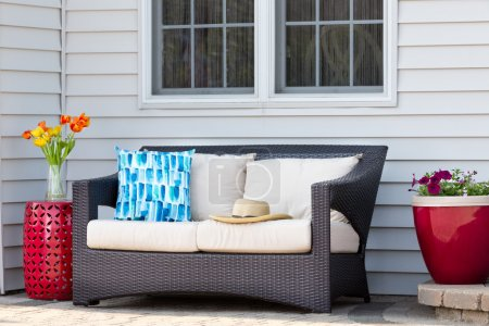 Photo pour Confortable espace de vie extérieur sur un patio en briques avec un siège profond et des coussins flanqués d'une table et d'un pot de fleurs en céramique rouge avec des fleurs printanières et un chapeau de soleil en paille - image libre de droit