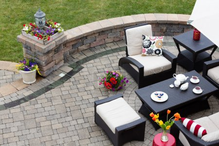 Photo pour Brick paved patio with comfortable patio furniture with modern armchairs and a stool around a table set with tea and cookies alongside a low curving wall overlooking a green lawn, high angle view - image libre de droit