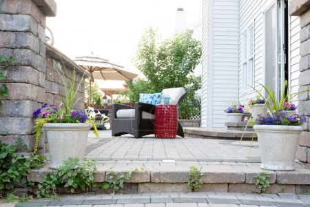Photo pour Low Angle View of Comfortable Furniture on Luxury Stone Patio of Affluent Home on Sunny Day - image libre de droit