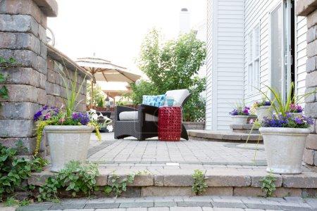 Photo pour Vue basse d'angle des meubles confortables sur le patio en pierre de luxe de la maison riche le jour ensoleillé - image libre de droit