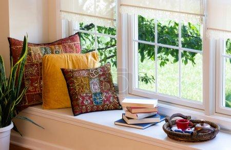 Foto de Taza de café en una bandeja, libros apilados y almohadas cuadradas en el rincón de lectura dentro de la casa. - Imagen libre de derechos