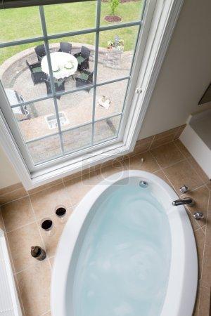 Modern bathtub overlooking a brick patio