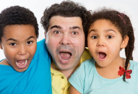 Photo for Close up Surprised Dad with Two Cute Kids Looking at the Camera with Mouth Wide Open Against White Background, Emphasizing Multicultural Family. - Royalty Free Image