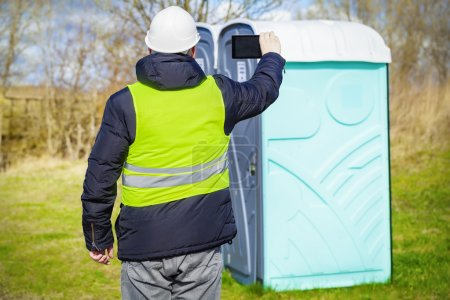 Photo for Inspector filmed on the tablet PC near portable toilets - Royalty Free Image