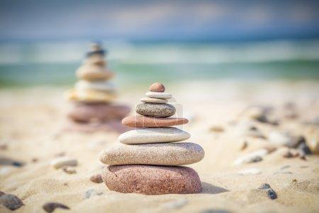 Photo pour Pierres équilibrées empilées sur un sable près de la mer - image libre de droit