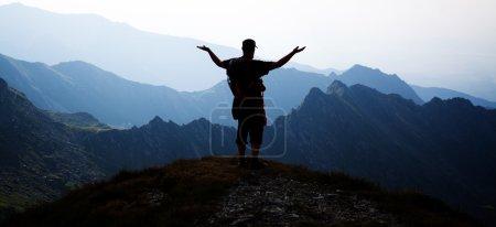 Photo pour Randonneur sur le pic admirant les montagnes rocheuses environnantes - image libre de droit