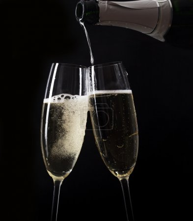 Photo for Champagne pouring in two glasses from a bottle - Royalty Free Image