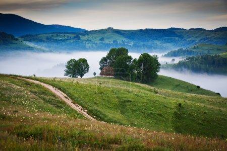 Photo pour Paysage estival avec un village de montagne dans la brume - image libre de droit