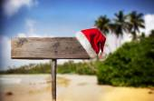 Wooden signboard with Christmas hat on tropical beach