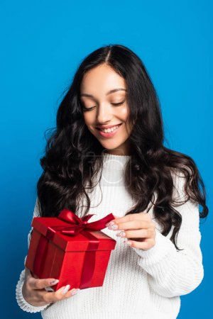 Photo for Happy woman in sweater touching ribbon on christmas present isolated on blue - Royalty Free Image