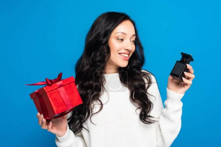 Photo for Happy woman in sweater holding christmas gift box and looking at bottle with perfume isolated on blue - Royalty Free Image