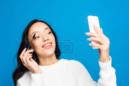 Photo for Joyful brunette woman applying mascara and looking at smartphone isolated on blue - Royalty Free Image