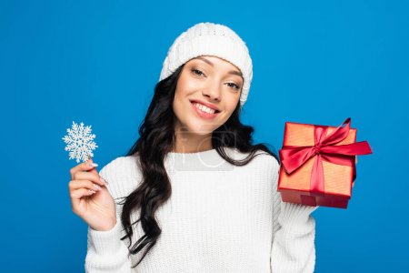 happy woman in knitted hat holding decorative snowflake and present isolated on blue