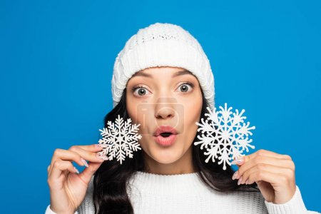 surprised woman in knitted hat holding decorative snowflakes isolated on blue
