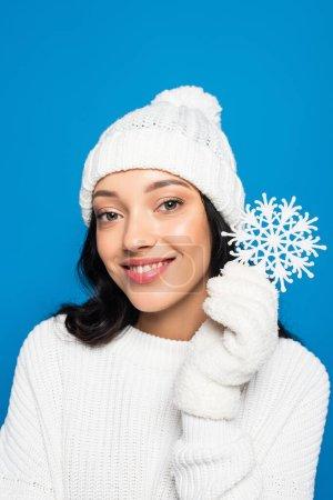 Photo pour Femme heureuse en bonnet tricoté et gants tenant flocon de neige décoratif isolé sur bleu - image libre de droit