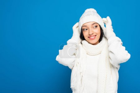 happy woman in winter outfit looking away isolated on blue