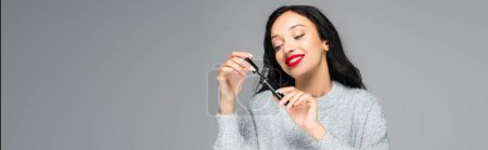 Photo for Happy brunette woman with red lips looking at mascara isolated on grey, banner - Royalty Free Image