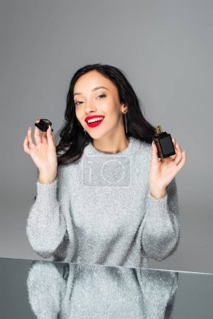 happy woman with red lips holding bottle with perfume isolated on grey