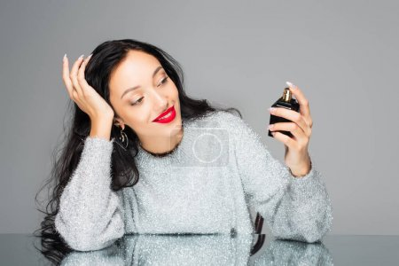 pleased woman with red lips holding bottle with perfume isolated on grey