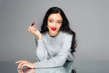 young pleased woman with red lips holding lipstick isolated on grey