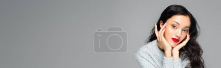 Photo for Brunette woman with red lips looking at camera isolated on grey, banner - Royalty Free Image