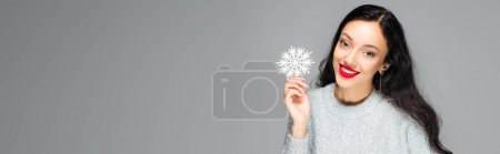 pleased woman with red lips holding decorative snowflake isolated on grey, banner