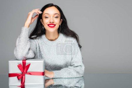 fröhliche Frau mit roten Lippen in der Nähe von Geschenkschachtel isoliert auf grau