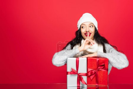 Photo for Joyful woman in hat and warm scarf showing hush sign near presents isolated on red - Royalty Free Image