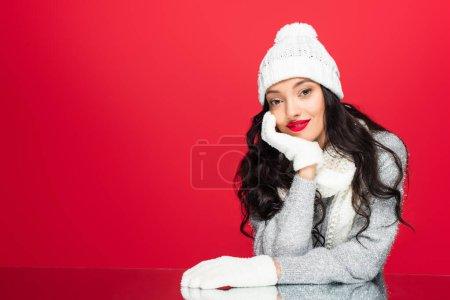 Junge Frau mit Hut und Handschuhen blickt vereinzelt in die Kamera