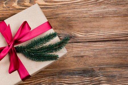 Photo for Top view of gift box with pink ribbon and pine branch on brown wooden background, new year concept - Royalty Free Image