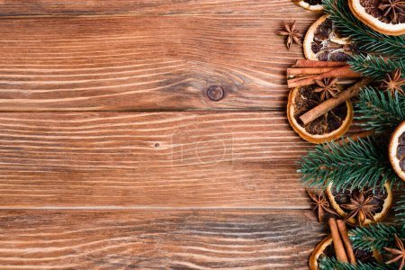 Top view of anise stars, dry orange slices, cinnamon sticks and pine branches on brown wooden background