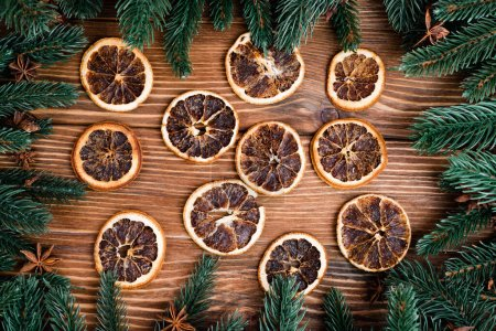 Photo for Flat lay with dry orange slices, pine branches and anise stars on brown wooden background, new year concept - Royalty Free Image