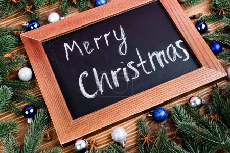 Photo pour Tableau avec des lettres de Noël joyeux, près des branches de pin, des boules et des étoiles d'anis sur fond de bois brun - image libre de droit