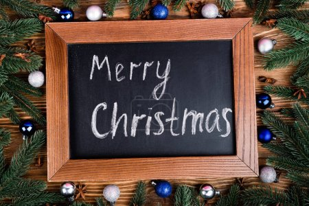 Top view of chalkboard with merry christmas lettering, pine branches, baubles and anise stars on brown wooden background